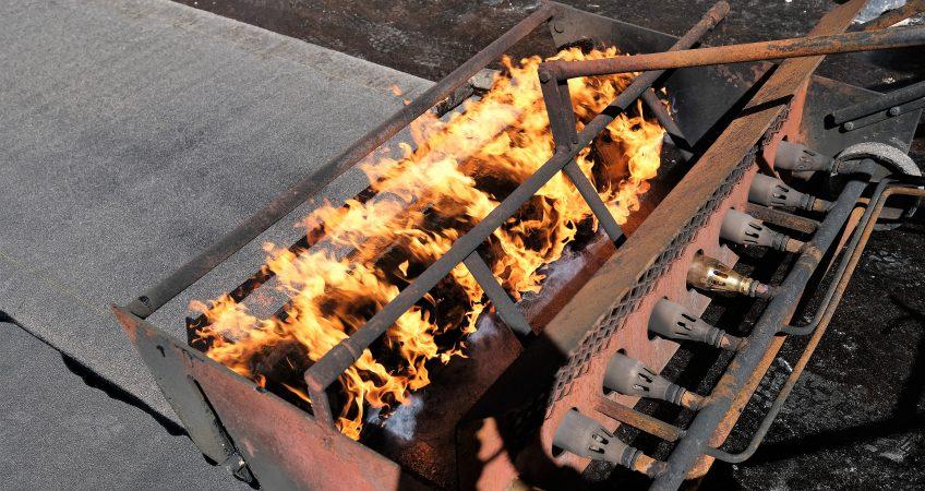 Tätskikt på rulle värms upp i brännarvagn